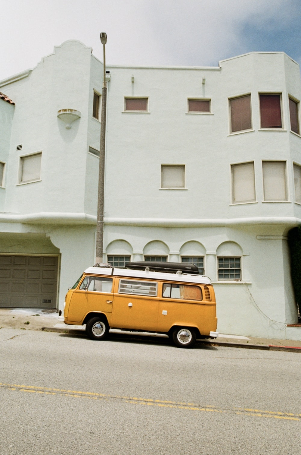 yellow and white van parked near white building