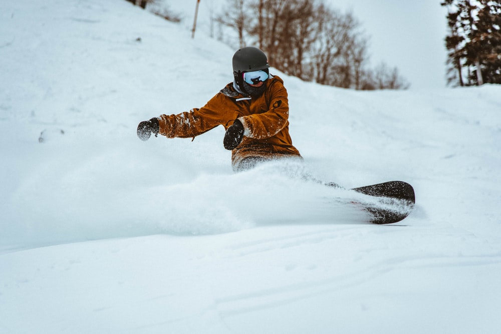 photography of person playing snowboarding during daytime