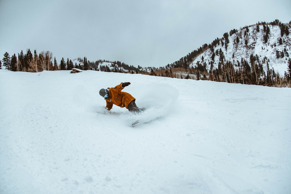 photography of person plying snowboarding during daytime