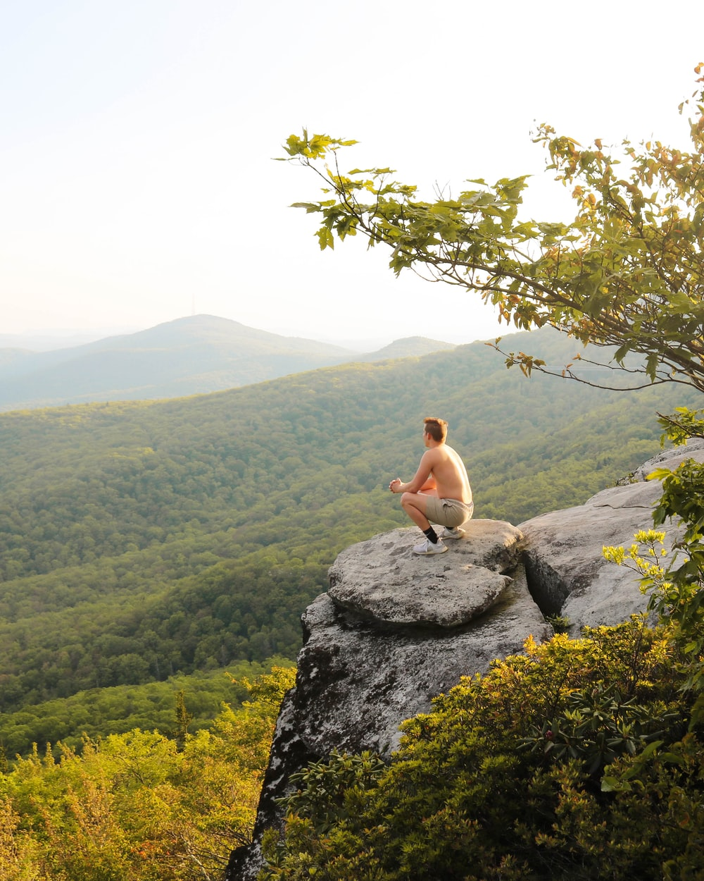man sitting on rock boulder