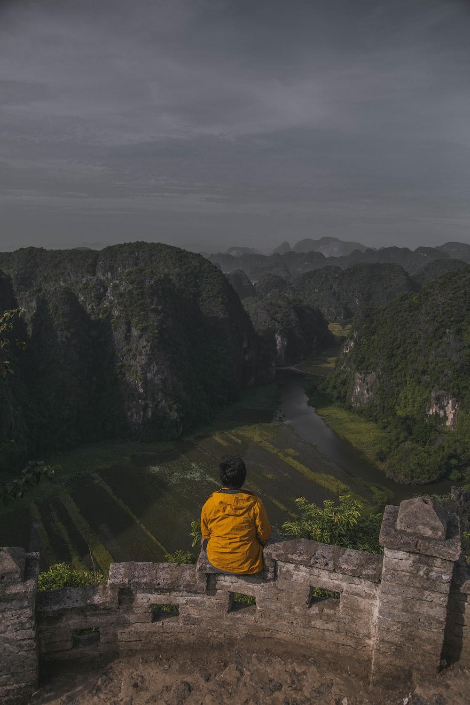 person wearing yellow jacket sitting on concrete edge