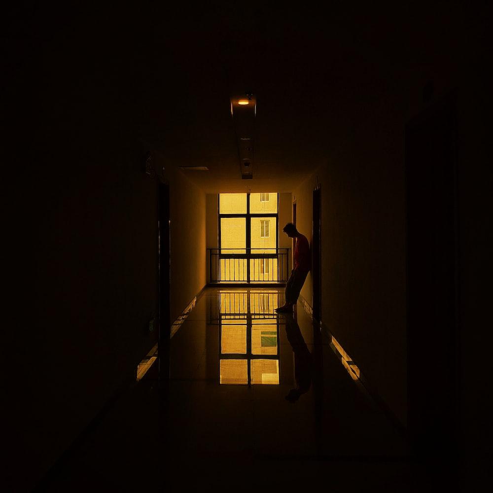man standing beside doorway