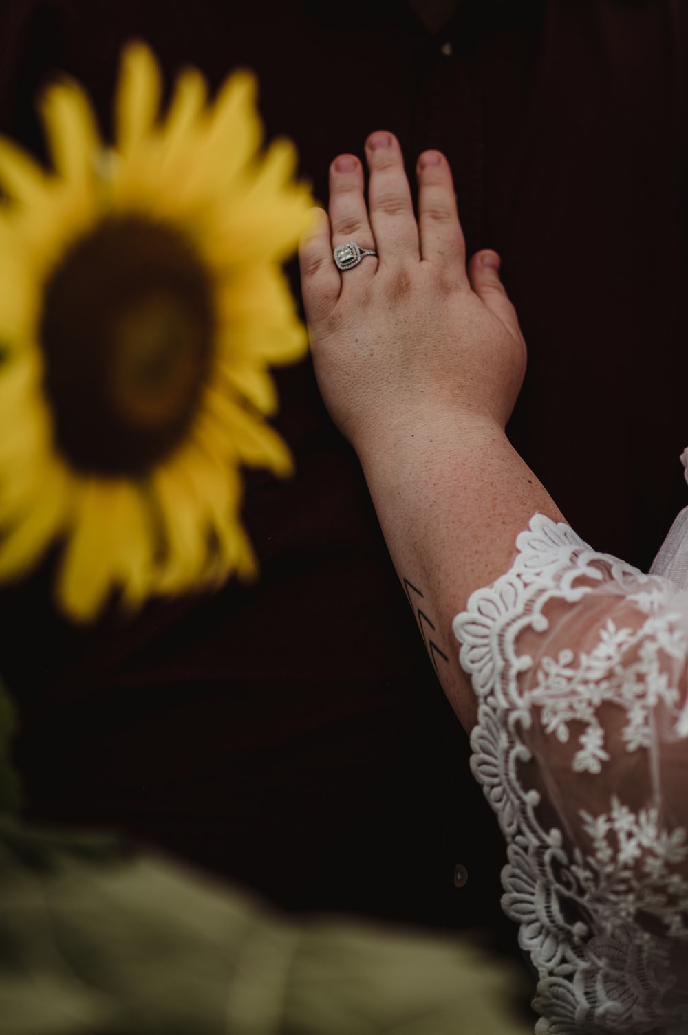 person wearing white floral lace top and silver-colored ring