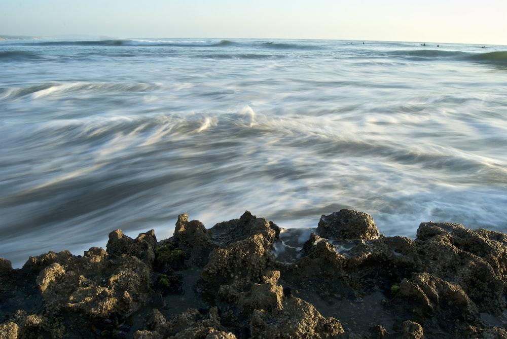 rippling body of water near brown rocks