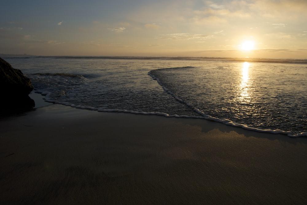 sea waves on seashore during sunset