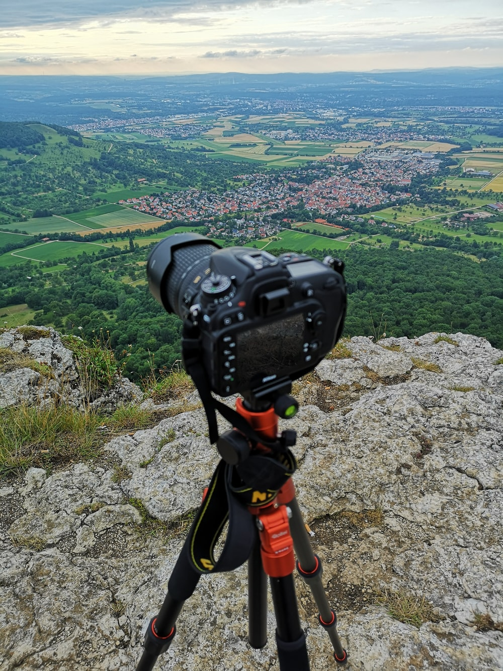 black DSLR camera on black and red tripod stand