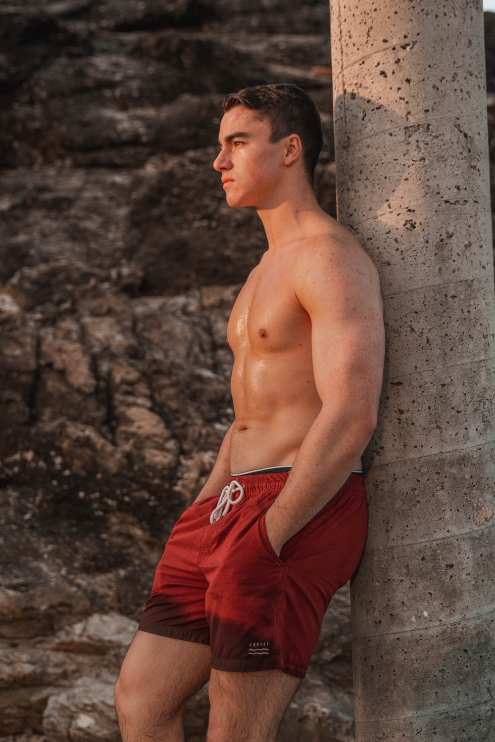 man wearing red boardshorts leaning on grey post