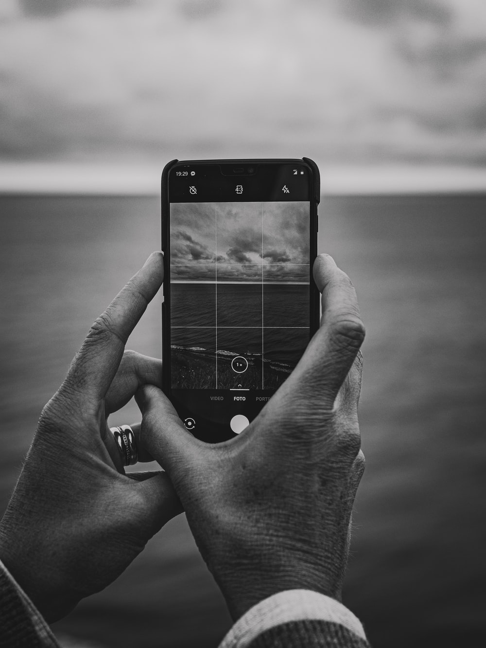 grayscale photography unknown person holding smartphone