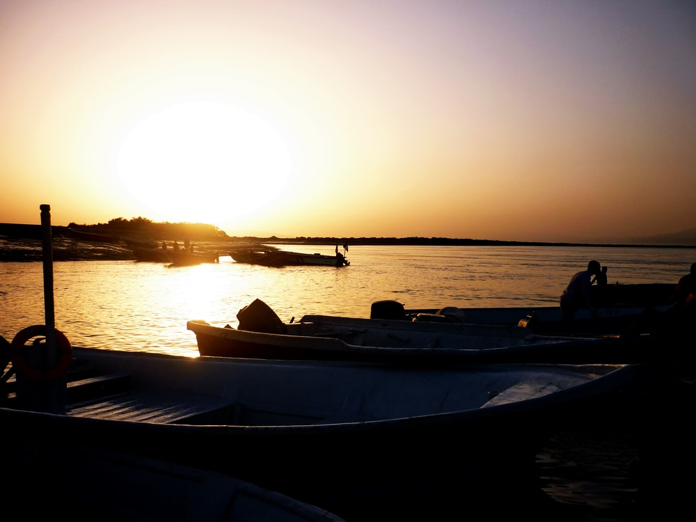 silhouette photography of boats on body of water