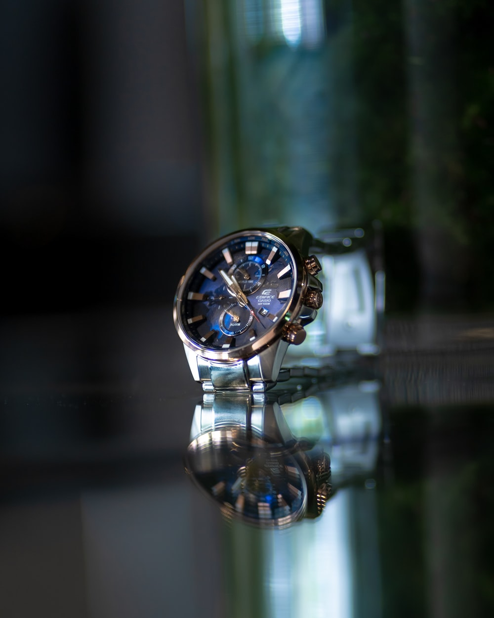 selective focus photography of round black and silver-colored chronograph watch
