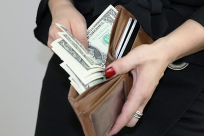 woman puts cash on her wallet