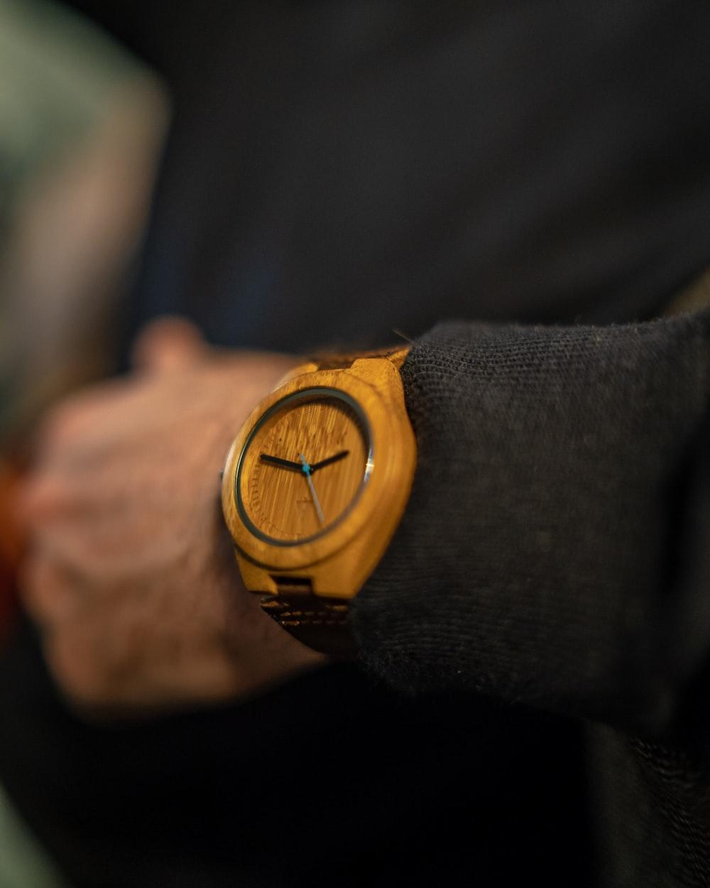 person wearing brown analog watch