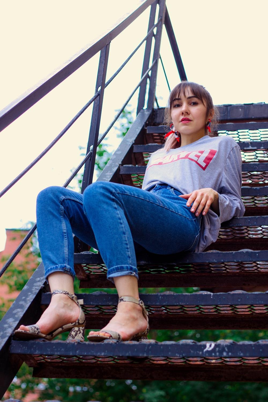 woman wearing grey jacket sitting on stair