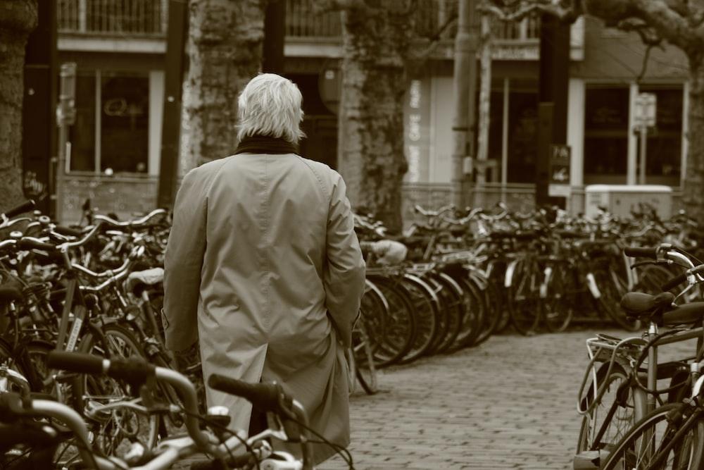man walking beside parked bikes