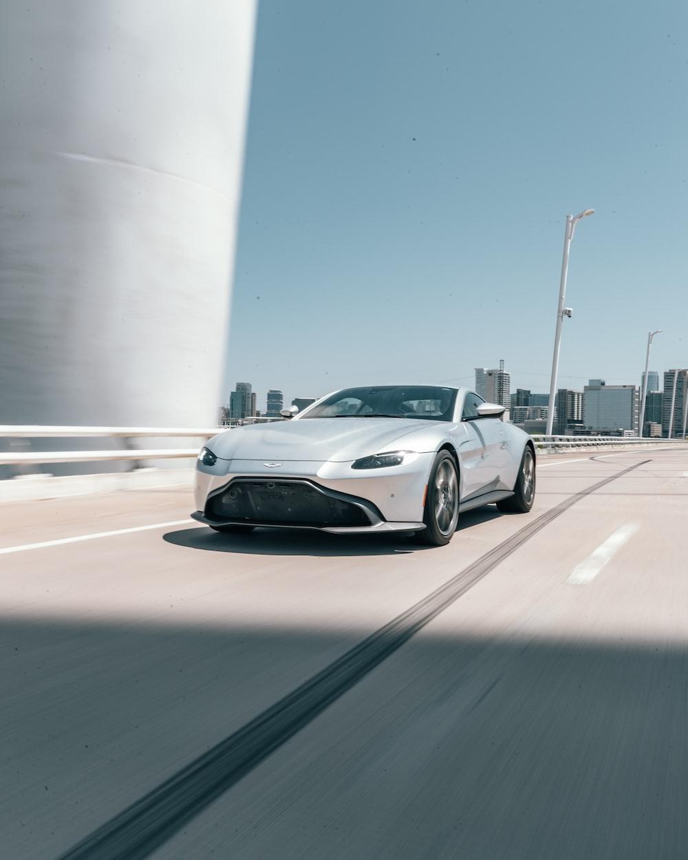 silver Aston Martin coupe runnin on road