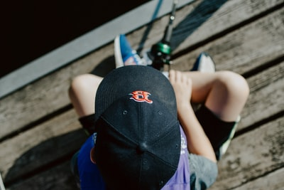 person wearing black cap holding fishing rod red sox zoom background