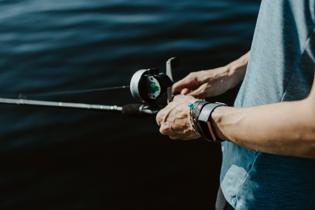 Hands holding a fishing pole with water background and bracelets