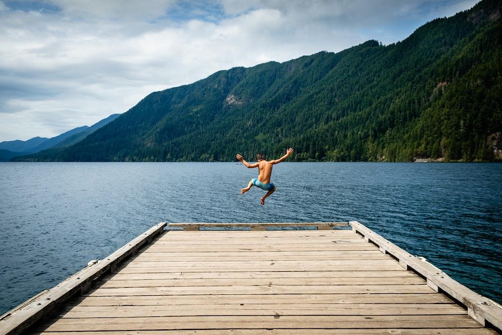 man jumping near sea