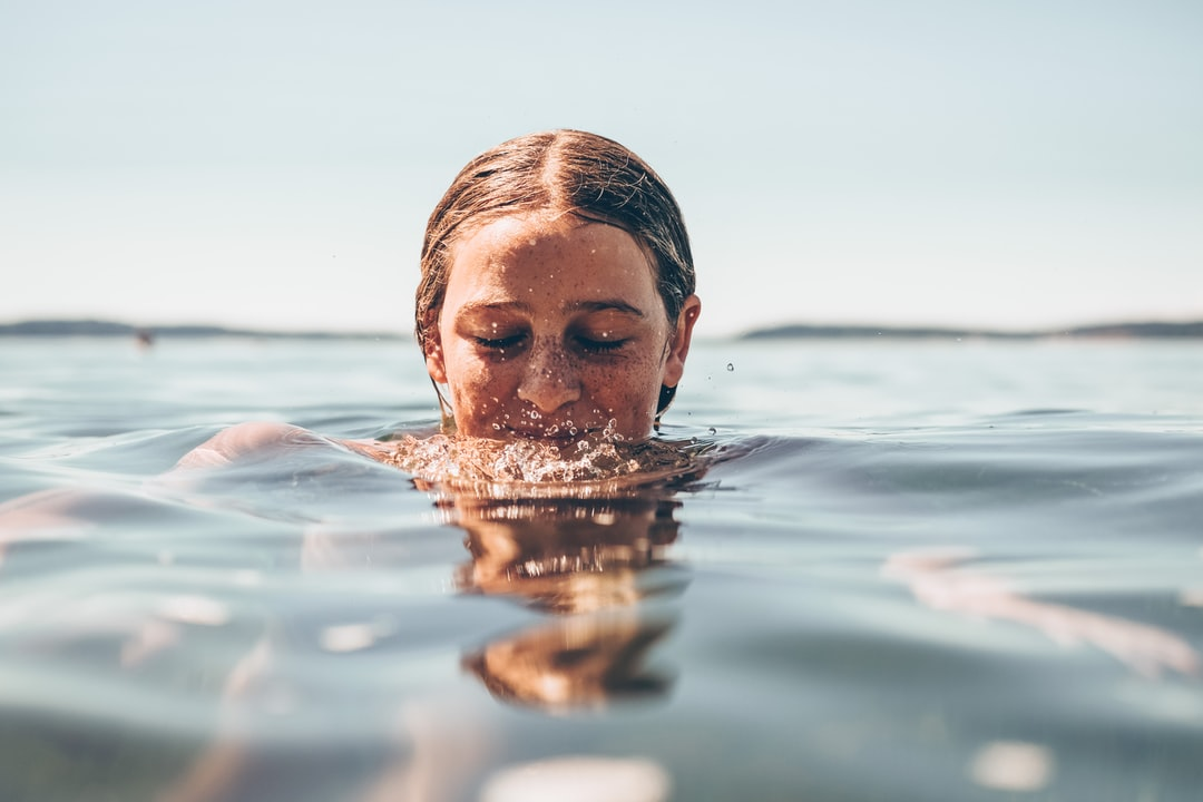 Teenage girl in the ocean with her head partially out of the water.