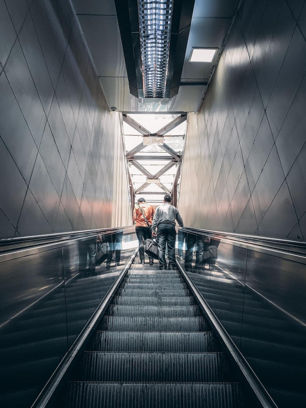 two men standing on elevator