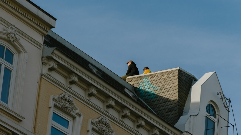 two person sitting on top of brown and white building