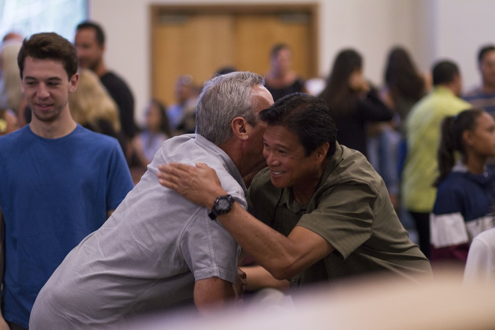 two men hugging on focus photography