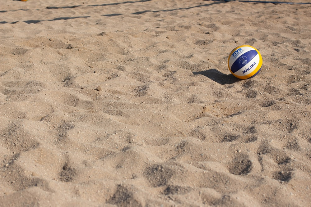 blue, yellow, and white volleyball on sand