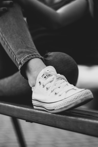grayscale photo of person in jeans and sneakers
