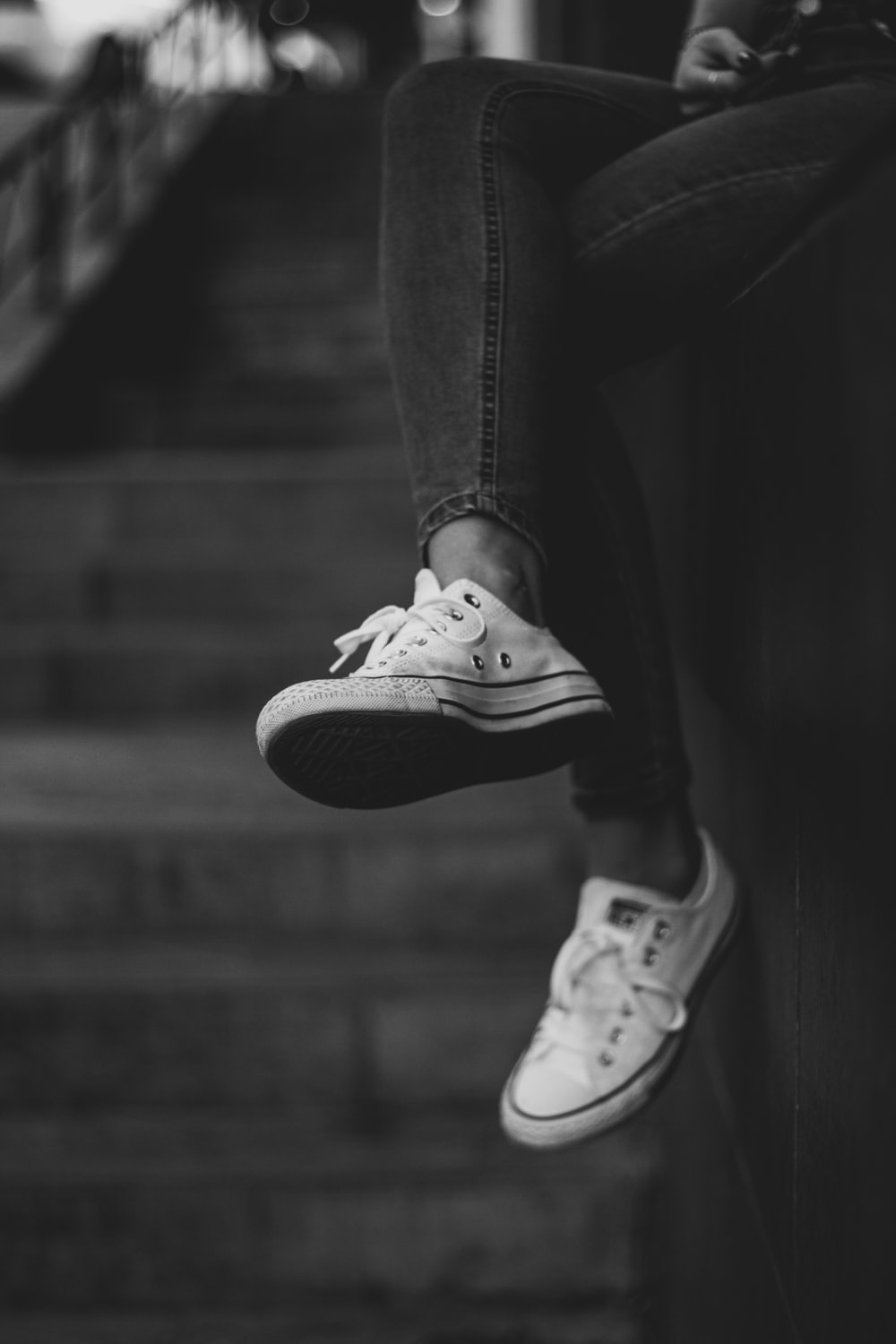 grayscale photography of person wearing jeans and sneakers