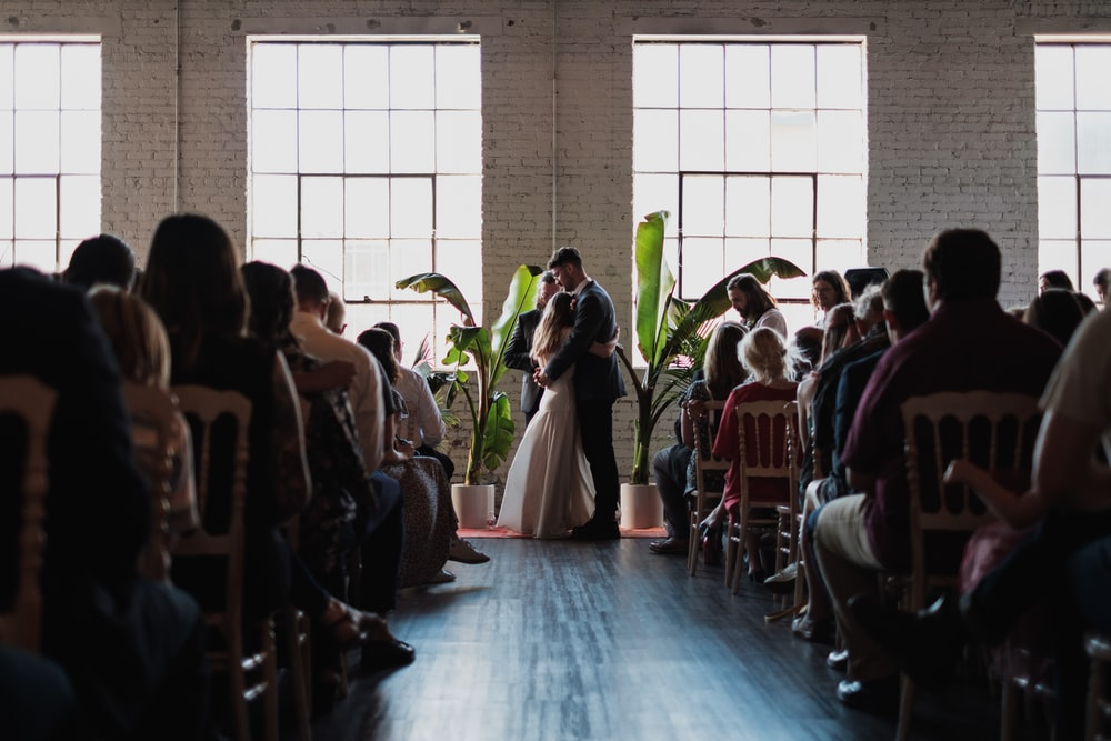 wedding couple hugging near people sitting inside building