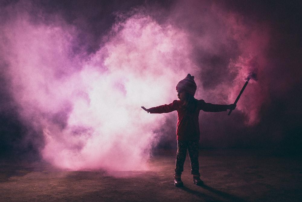 girl holding stick near smoke