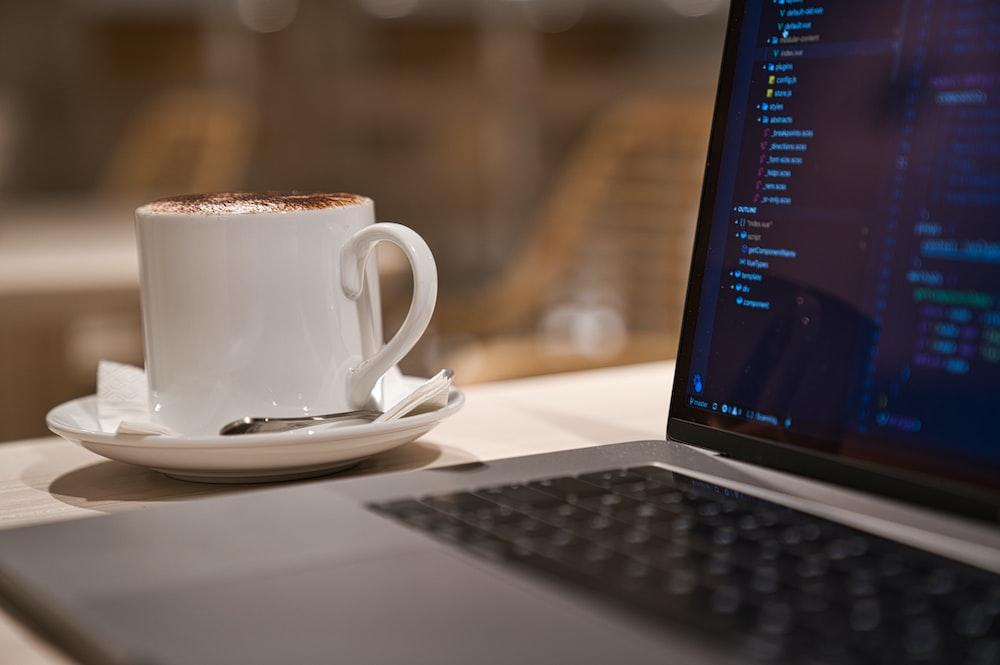 black laptop computer beside white ceramic mug close-up photography