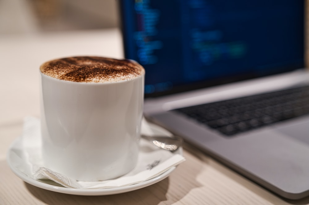 cappuccino in cup on saucer beside laptop