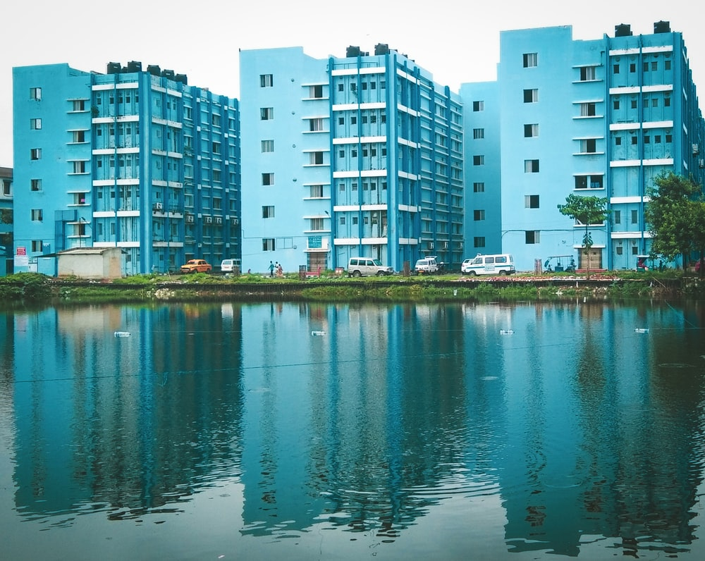 blue painted buildings beside body of water