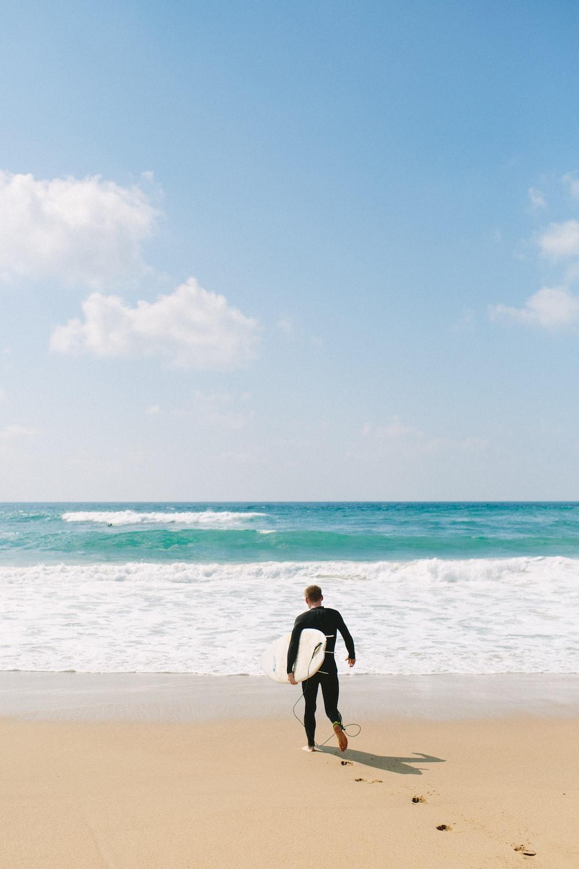 man carries surfboard towards shore