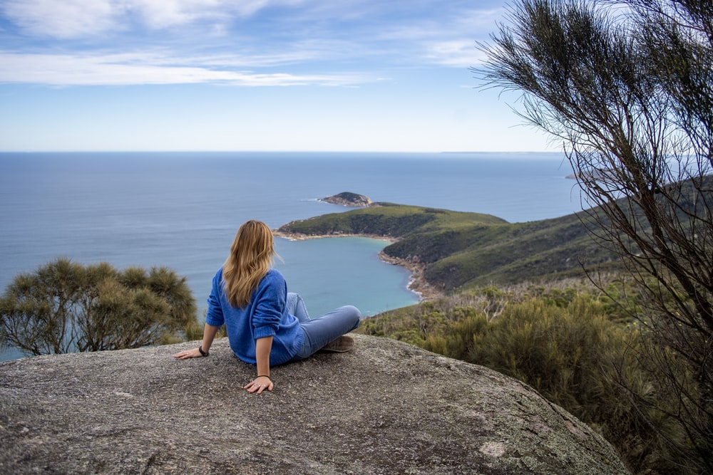 person sitting on gray rock during daytime