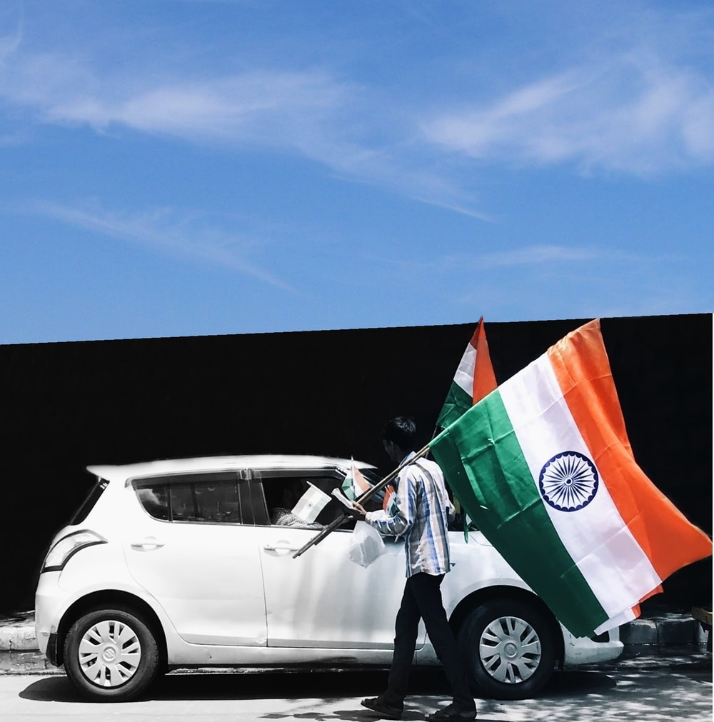 man holding flag of India beside white car