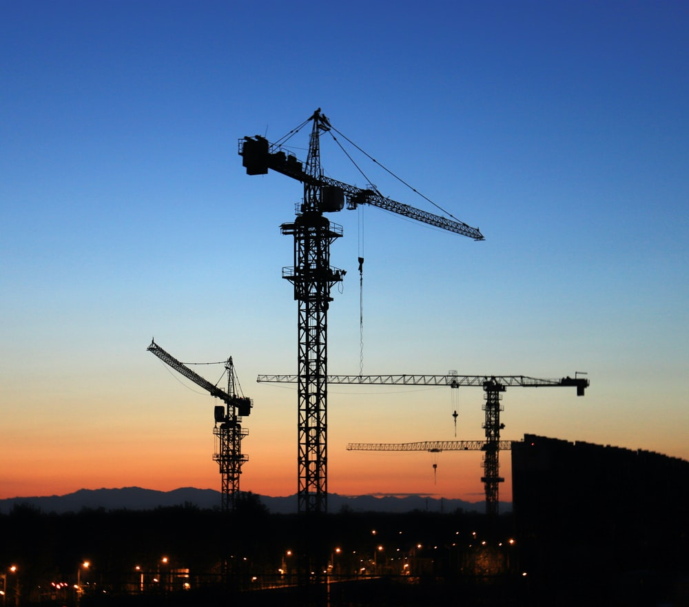 building site with tower cranes during golden hour
