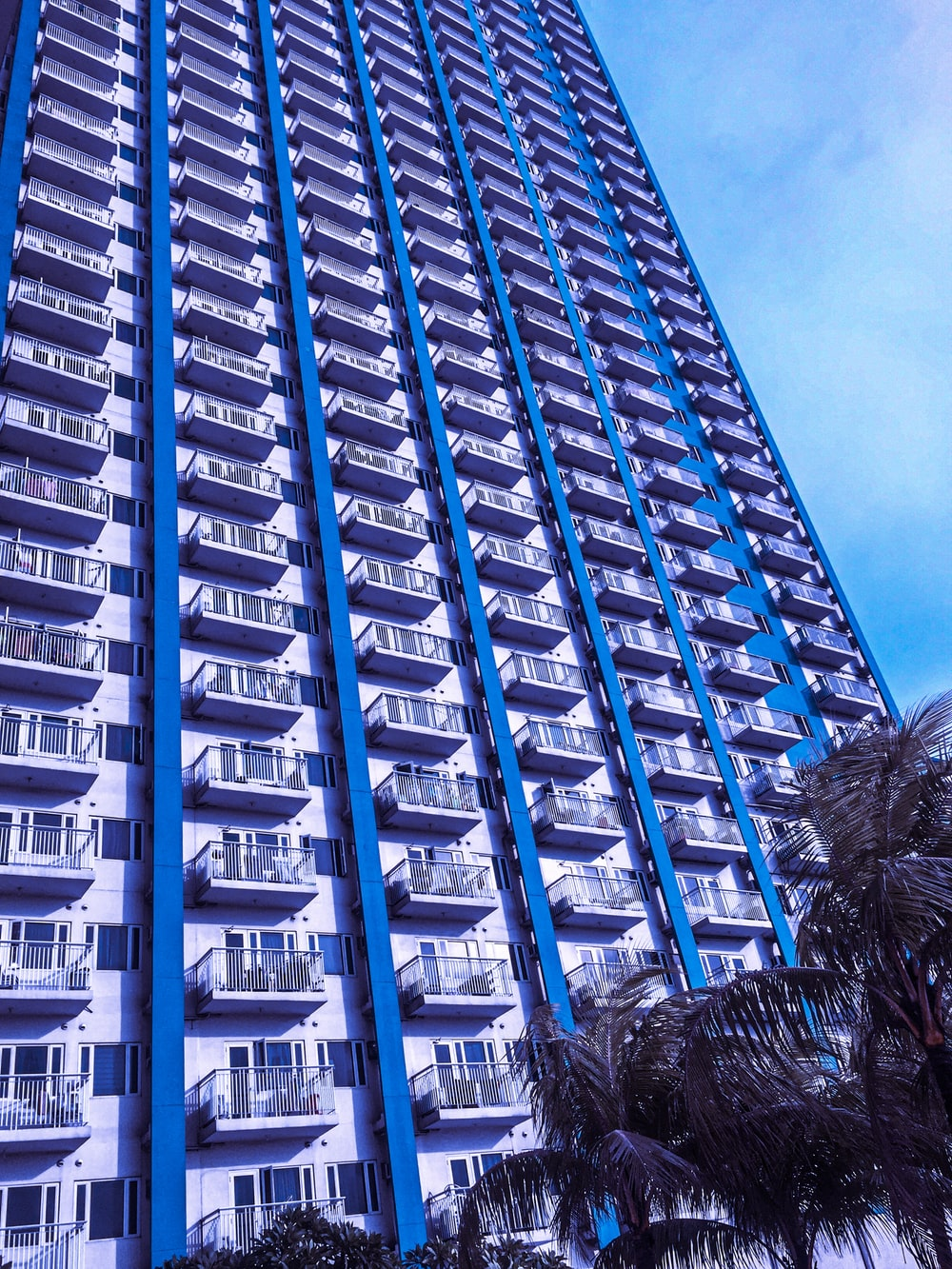 view of white and blue painted apartment complex