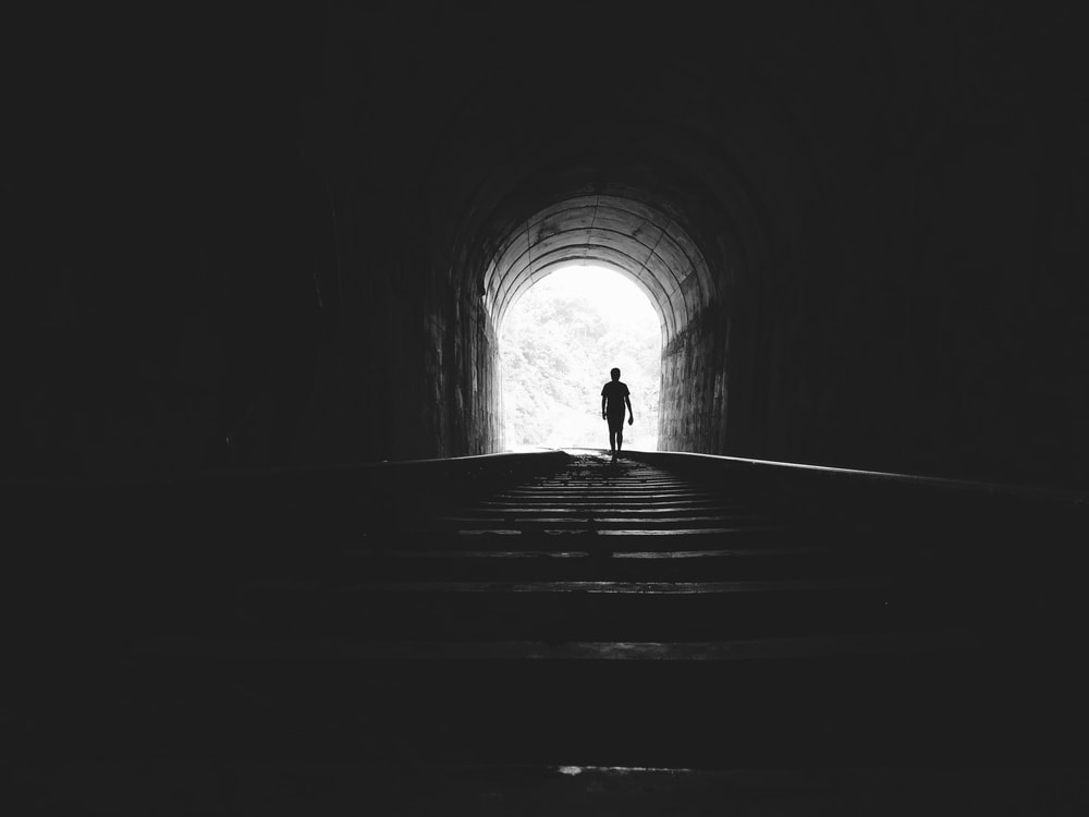 silhouette of man under tunnel