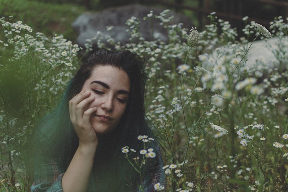 woman sitting on flowerfield