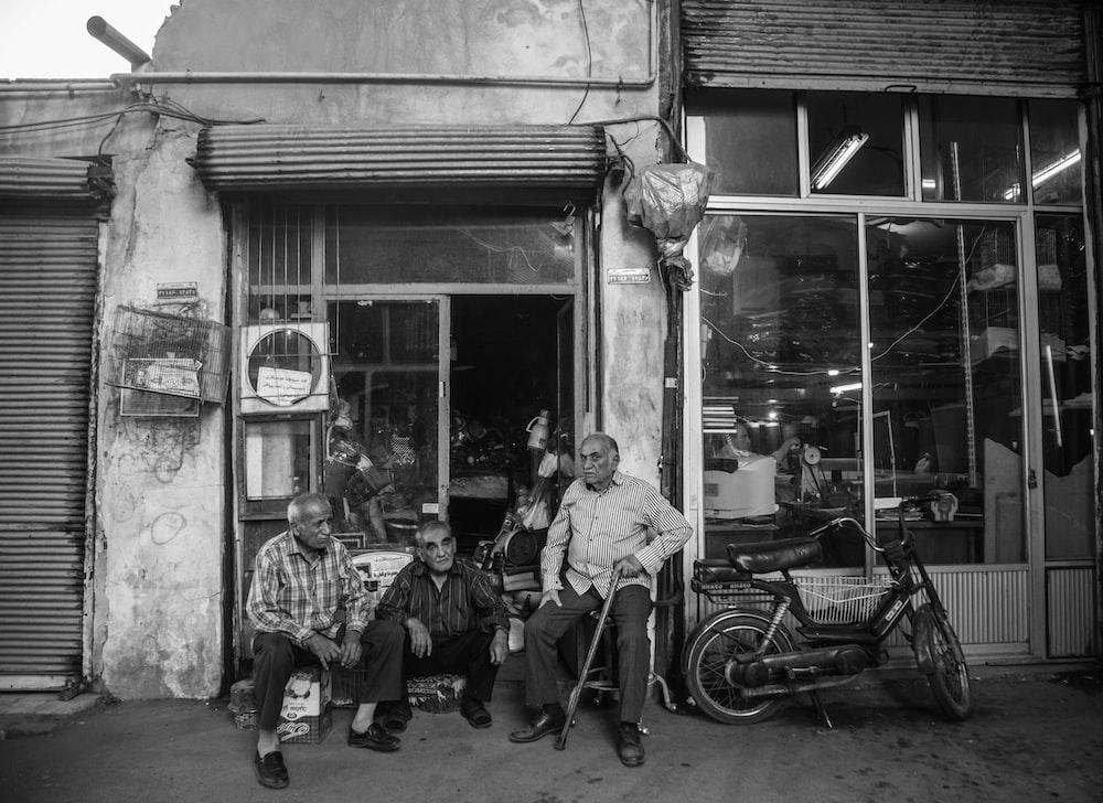 greyscale photography of men sitting beside door