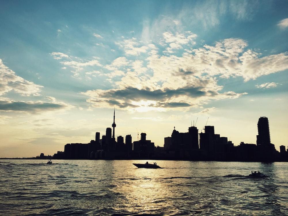 silhouette photo of buildings beside sea