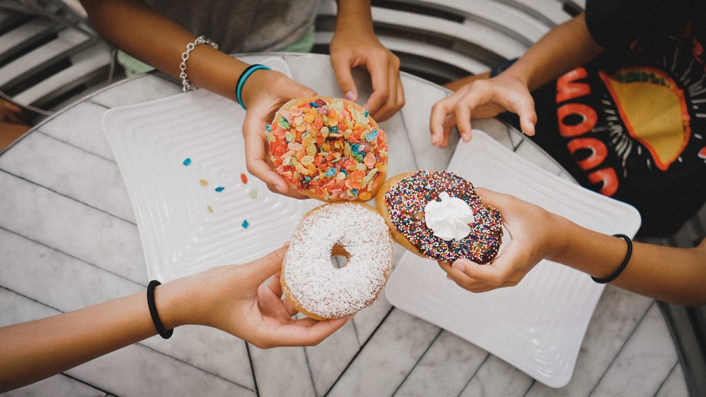 shallow focus photo of person holding donuts
