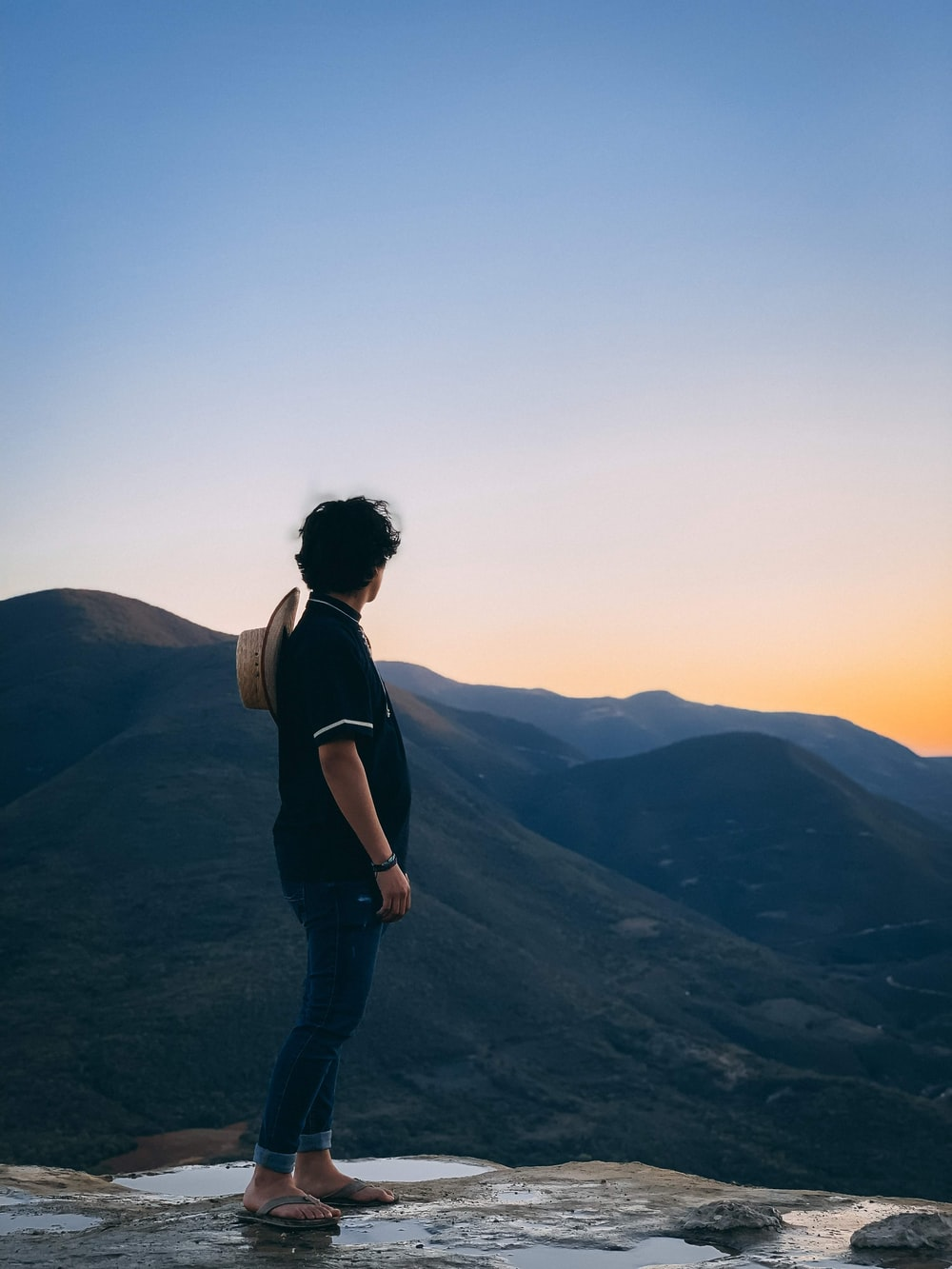 man standing on rocky hill facing mountain