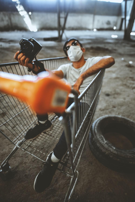 man riding on gray shopping cart close-up photography