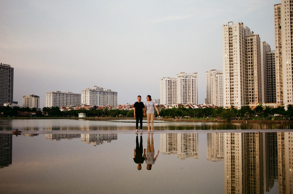 two person standing beside body of water near buildings during daytime