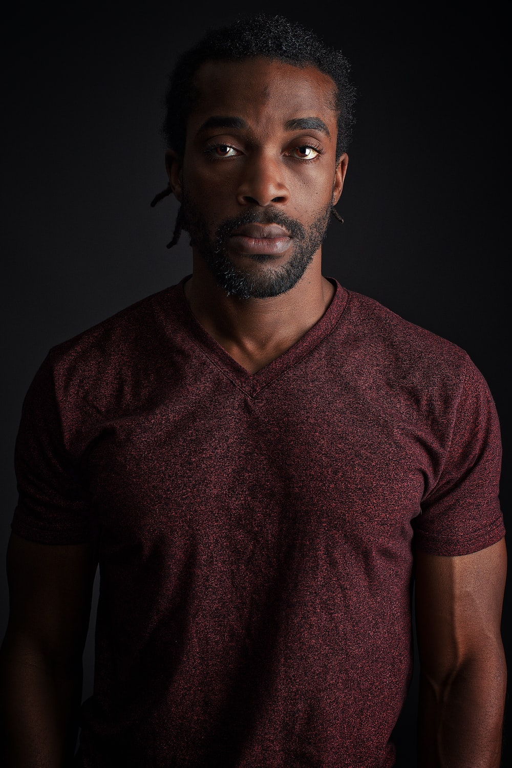 man wearing red v-neck shirt close-up photography