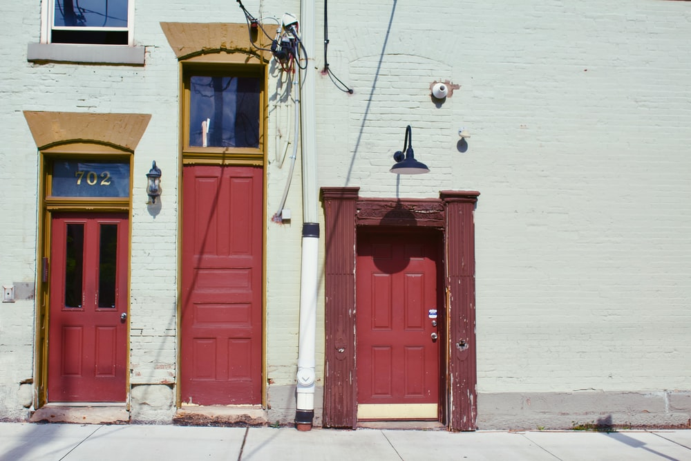 minimalist photography of three red wooden doors