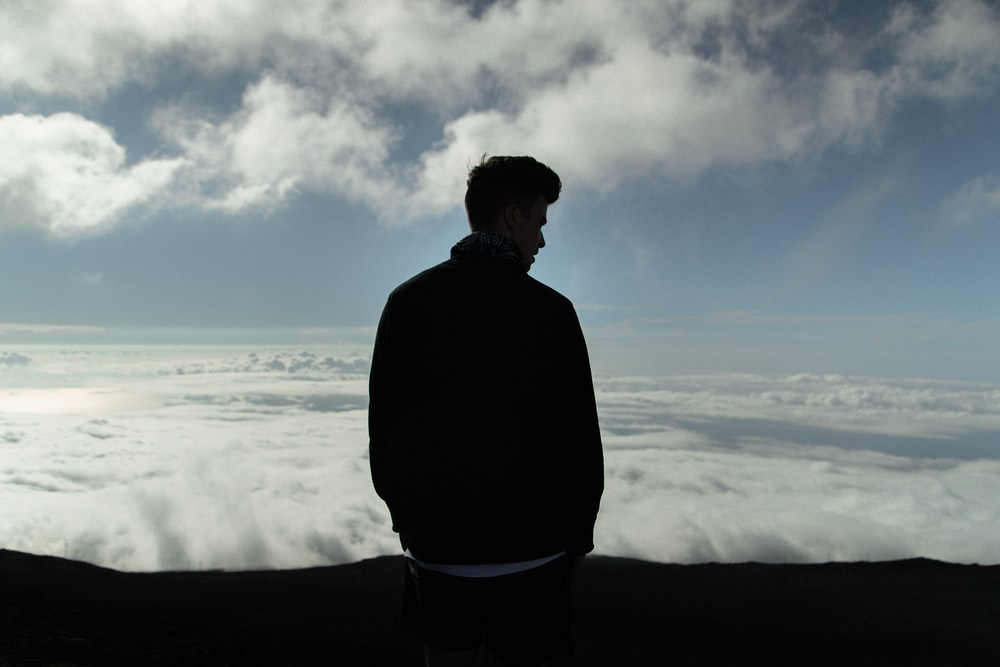 man standing with sea of clouds in background